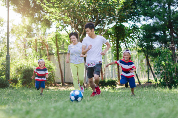 Family playing soccer in public park stock photo