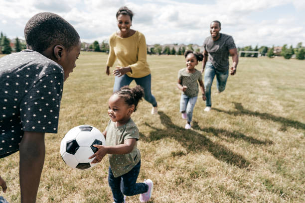 Family playing soccer outdoor stock photo