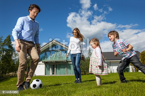 istock Family playing soccer outside 914484980