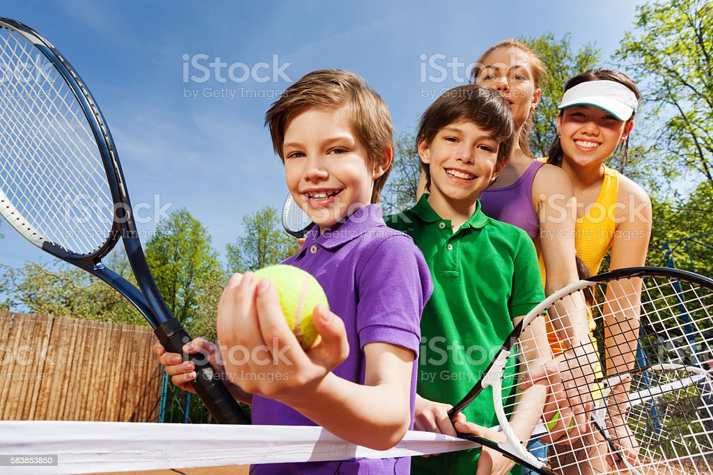 Family playing tennis holding rackets and ball stock photo