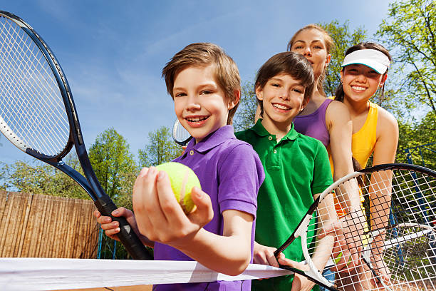 family playing tennis holding rackets and ball - knete spiele stock-fotos und bilder