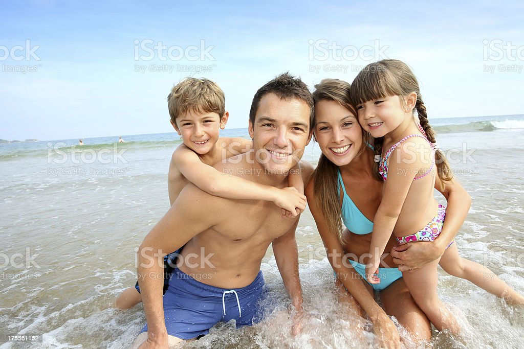 Family playing together in waves at the beach royalty-free stock photo