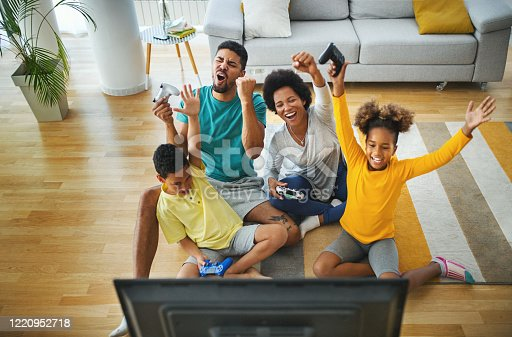 Closeup top view of a young african american family with two children spending time at home during coronavirus pandemic in 2020. They are playing some video games in the living room.  For later use this is a quite useful family lifestyle content.