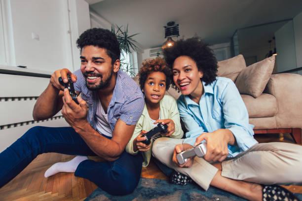 Familia jugando videojuegos juntos - foto de stock