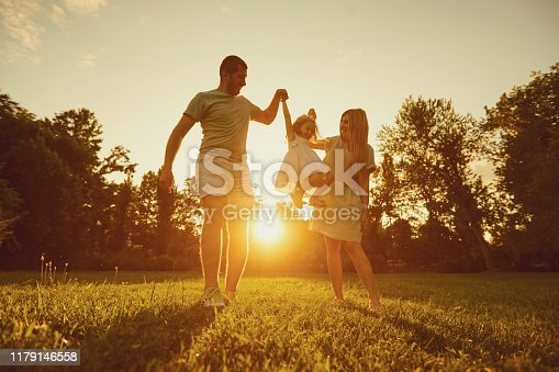 Family playing with a child at sunset with sunlight on the nature in the summer. Concept happy parents.