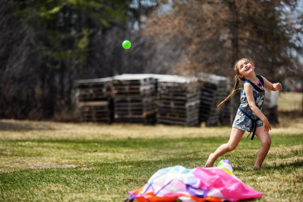 Family playing with a parachute filled with balls stock photo