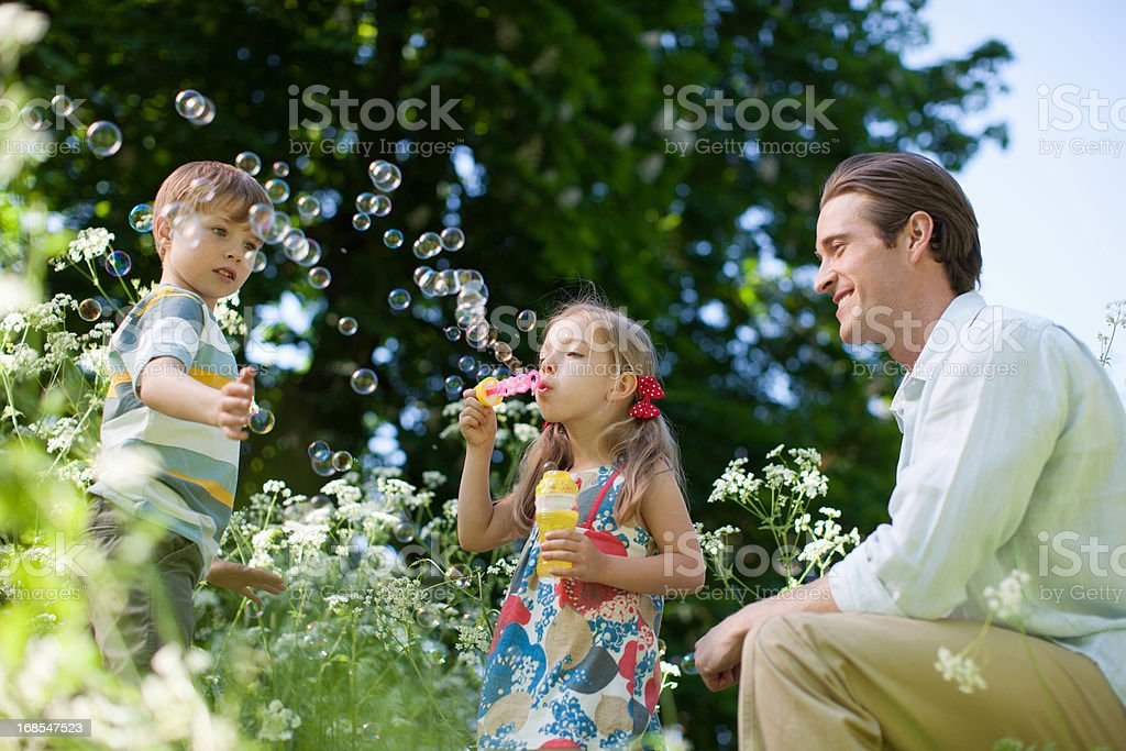 Family playing with bubbles outdoors royalty-free stock photo