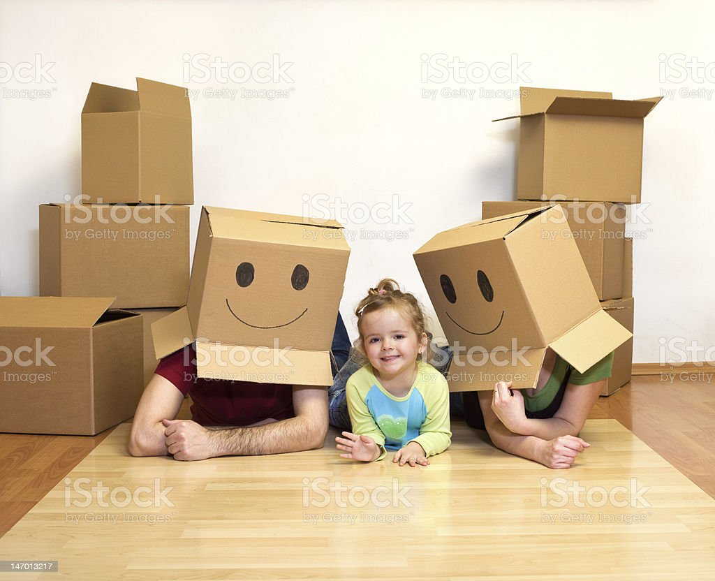 Family playing with cardboard boxes in their new home royalty-free stock photo
