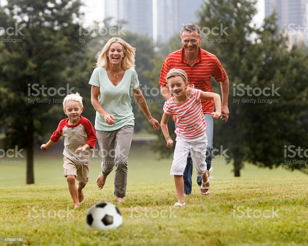 Family playing with children in park stock photo