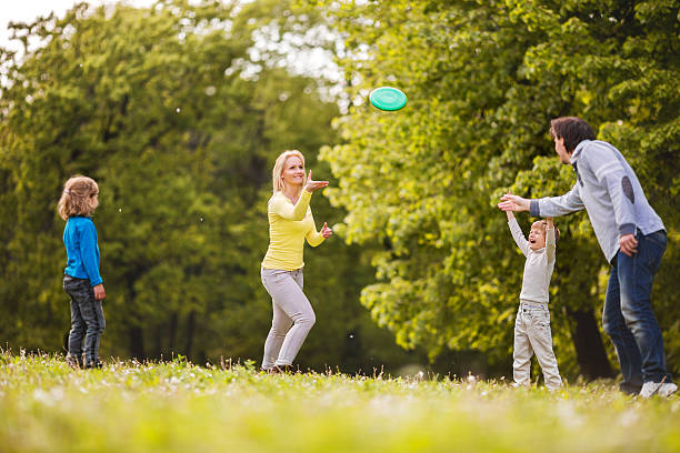 Family playing with friesbee in nature. Playful family having fun in the park while throwing a friesbee. plastic disc stock pictures, royalty-free photos & images