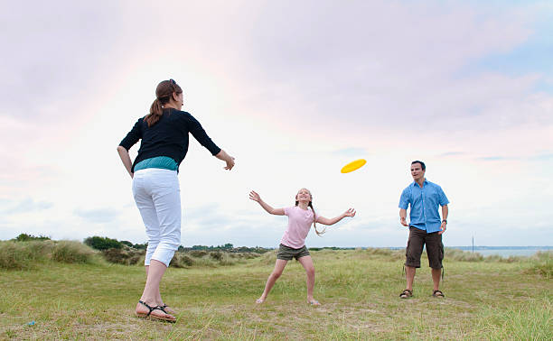 Family playing with frisbee outdoors  plastic disc stock pictures, royalty-free photos & images