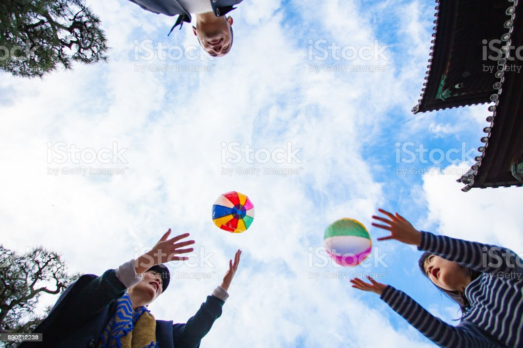 Family playing with paper balloon stock photo