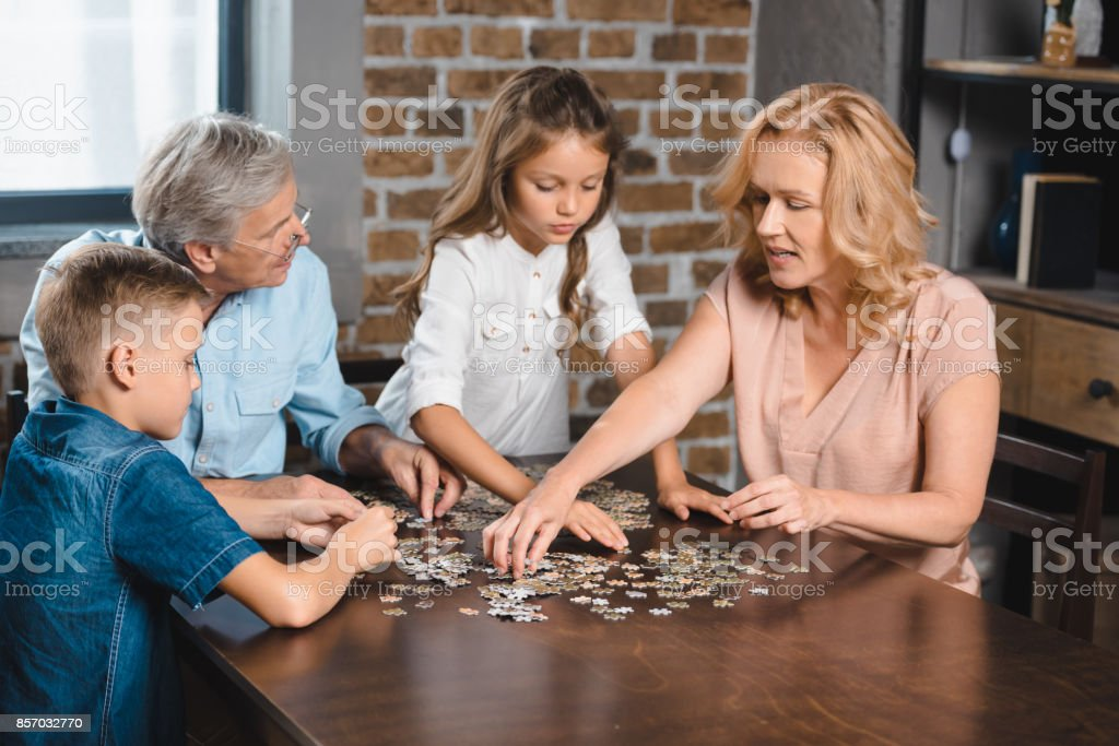 family playing with puzzle stock photo