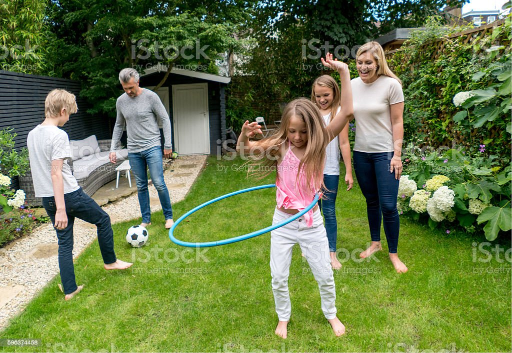 Family playing with the hula hoop outdoors stock photo