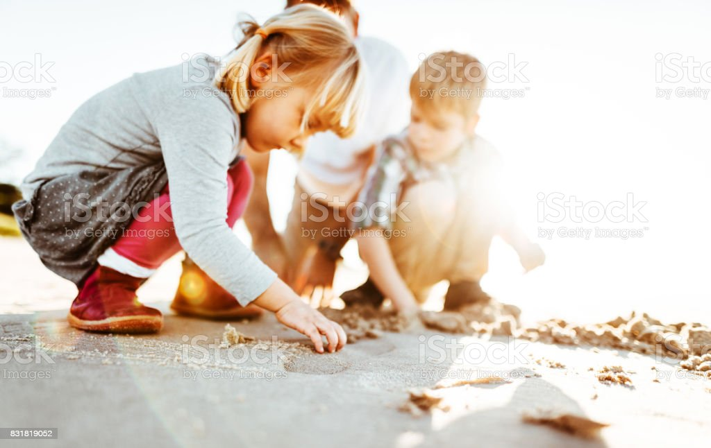 family playing with the sand on the beach stock photo