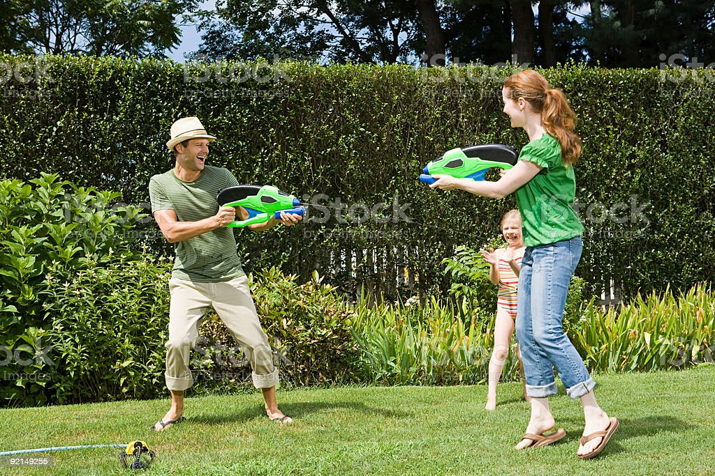 Family playing with water pistols stock photo