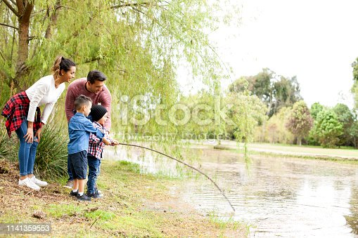 509813720 istock photo Family plays around the lake 1141359553