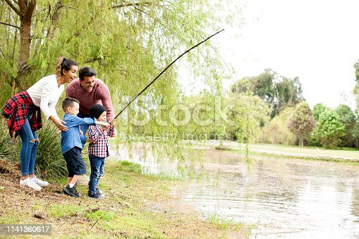 509813720 istock photo Family plays around the lake 1141360617