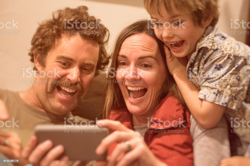 Family plays on funny phone app while laughing stock photo