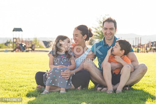 Mom, dad, and their two young kids pose on the grass at the playground for a family picture on a beautiful summer afternoon. The playground is behind them. All of them are looking at each other and smiling and laughing.