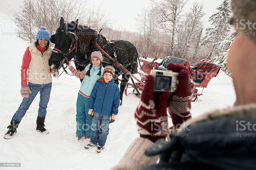 Family portrait by horse drawn sleigh stock photo