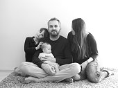 lifestyle shot of family with little boy and baby girl posing indoors.monochrome shot.