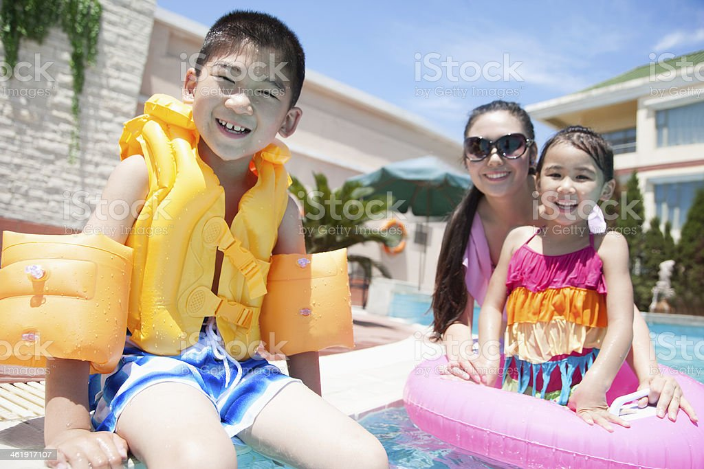 Family portrait, mother, daughter, and son, by the pool stock photo