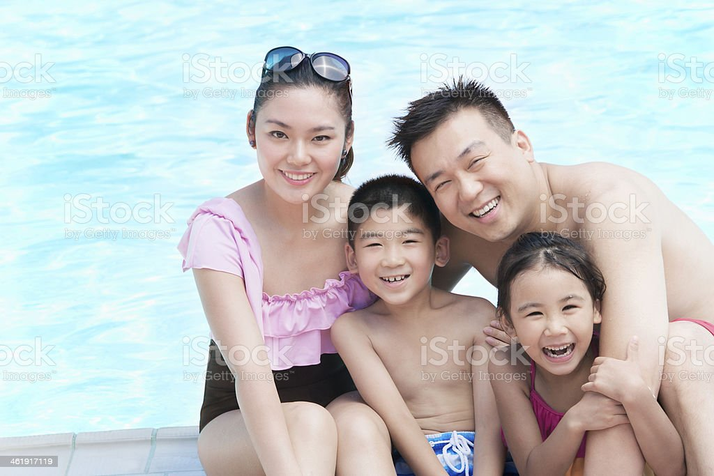 Family portrait, mother, father, daughter, and son, smiling by pool stock photo