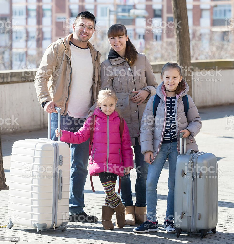 Family portrait of travellers with wheeled trollers in spring da stock photo
