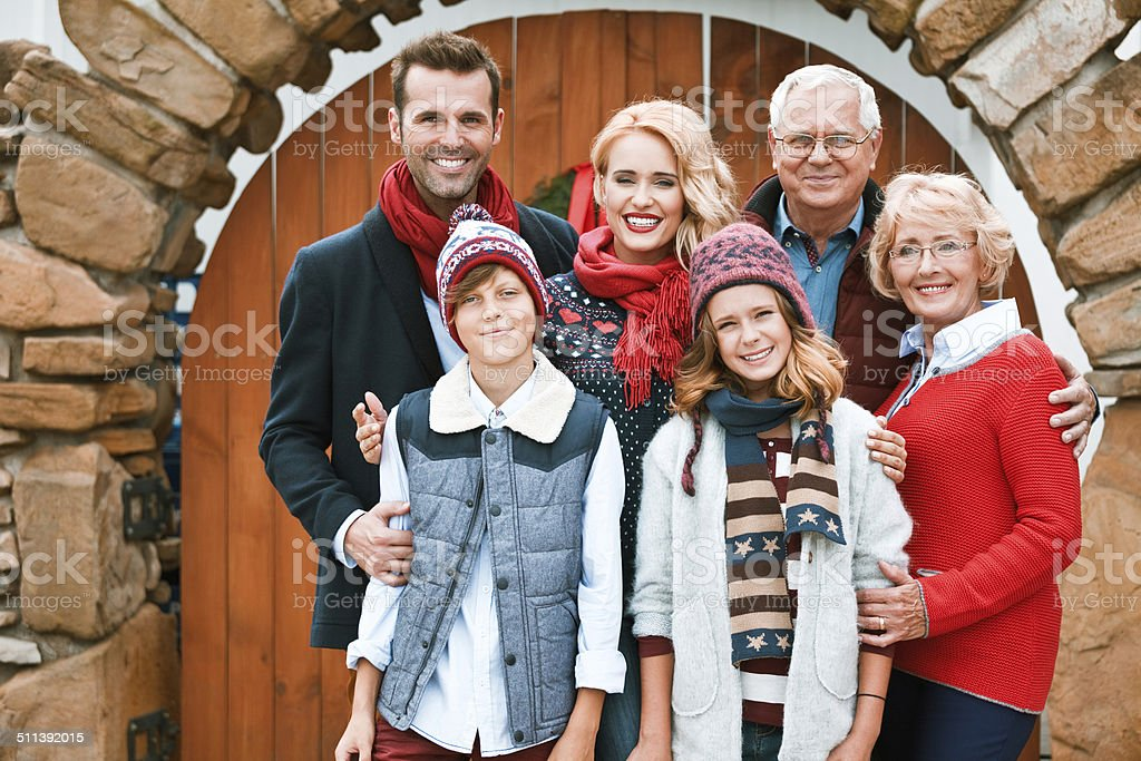 Family Portrait Winter portrait of happy multi generation family: grandparents, parents and children standing in front of entrance door. Active Seniors Stock Photo