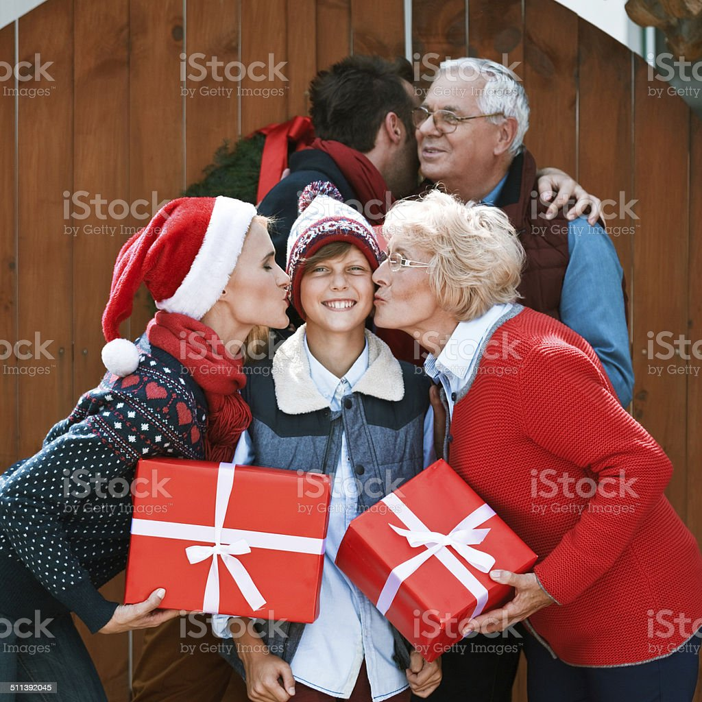 Family Portrait Winter portrait of happy multi generation family. Mother and grandmother holding christmas gifts and kissing a cheerful boy. Active Seniors Stock Photo