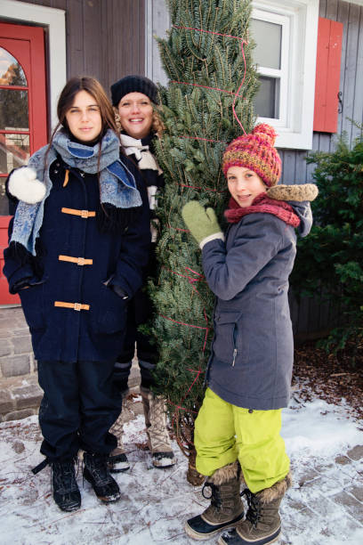 Family portrait with freshly cut Christmas tree in front of house outdoors. Family portrait with freshly cut Christmas tree in front of house outdoors. There is a bit of fresh snow on the ground. Family of mother, and two teenage girls. Vertical full length outdoors shot with copy space. This was taken in Quebec, Canada. 12 17 months stock pictures, royalty-free photos & images