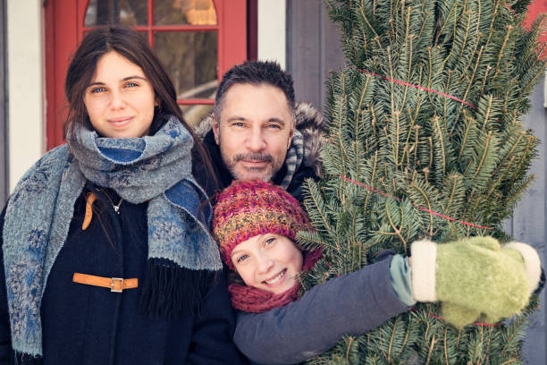 Family portrait with freshly cut Christmas tree in front of house outdoors. Family portrait with freshly cut Christmas tree in front of house outdoors. Family of father and two teenage girls, looking at the camera. Horizontal waist up outdoors shot with copy space. This was taken in Quebec, Canada. 12 17 months stock pictures, royalty-free photos & images