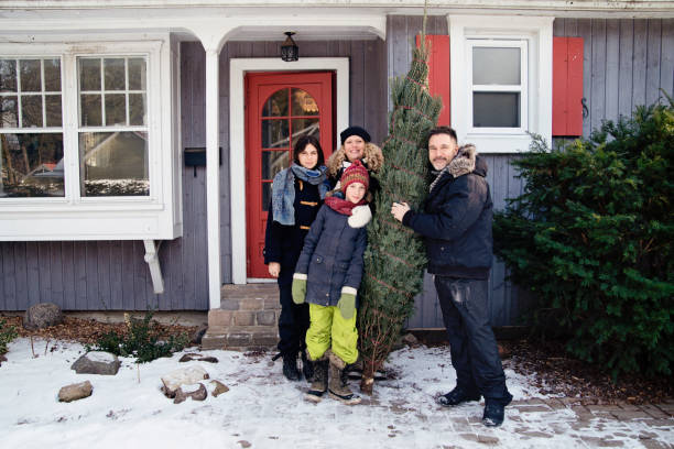 Family portrait with freshly cut Christmas tree in front of house outdoors. Family portrait with freshly cut Christmas tree in front of house outdoors. There is a bit of fresh snow on the ground. Family of mother, father and two teenage girls. Horizontal full length outdoors shot with copy space. This was taken in Quebec, Canada. 12 17 months stock pictures, royalty-free photos & images