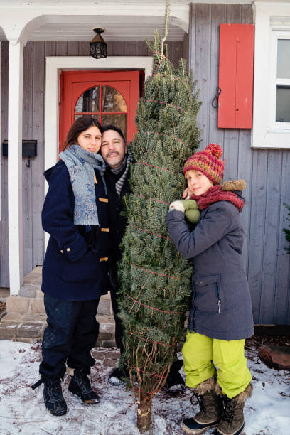 Family portrait with freshly cut Christmas tree in front of house outdoors. Family portrait with freshly cut Christmas tree in front of house outdoors. Family of father and two teenage girls, looking at the camera. Vertical full length outdoors shot with copy space. This was taken in Quebec, Canada. 12 17 months stock pictures, royalty-free photos & images