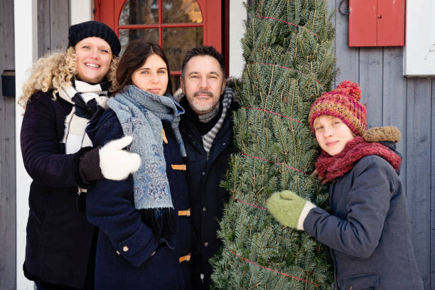 Family portrait with freshly cut Christmas tree in front of house outdoors. Family portrait with freshly cut Christmas tree in front of house outdoors. There is a bit of fresh snow on the ground. Family of mother, father and two teenage girls. Horizontal waist up outdoors shot with copy space. This was taken in Quebec, Canada. 12 17 months stock pictures, royalty-free photos & images