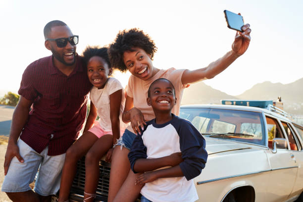 family posing for selfie next to car packed for road trip - family vacation stock photos and pictures