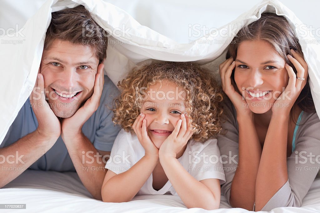Family posing under a duvet stock photo