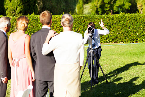 Family posing while man photographing them at garden wedding picture id450310929?b=1&k=6&m=450310929&s=612x612&w=0&h=xwlf7jqzypmh0h3a9mlfyfefwhe yctjrjuicv8pvo4=