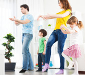 Family with two children practicing tai chi at home, father showing them how to practice. Real people, togetherness, healthy lifestyle.