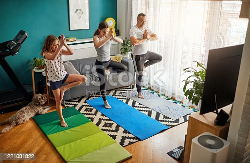 istock Family Practicing Yoga At Home With Online Classes 1221031822
