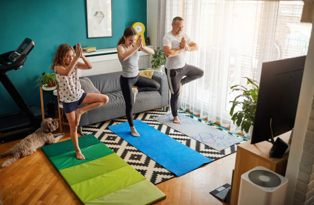 Family Practicing Yoga At Home With Online Classes stock photo