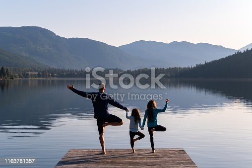 Family practising yoga outdoors. Healthy lifestyle spending time outdoors.
