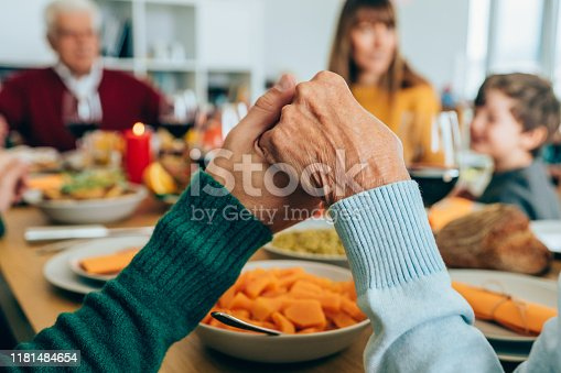 Close-up shot of a people holding hands in prayer before having a holiday dinner or lunch.