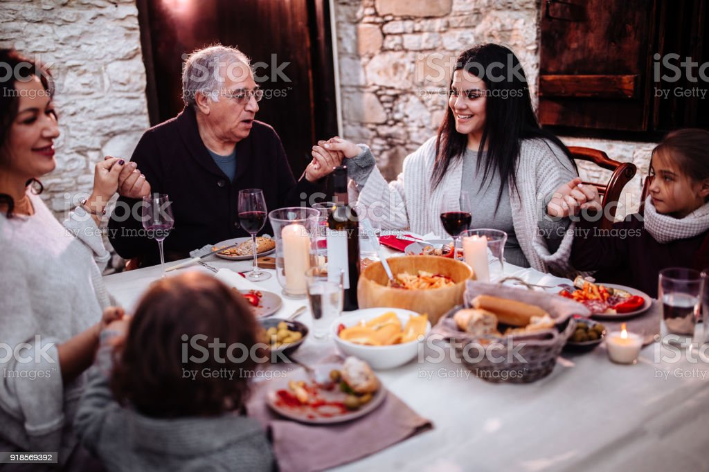 Family praying and holding hands before lunch at traditional house stock photo