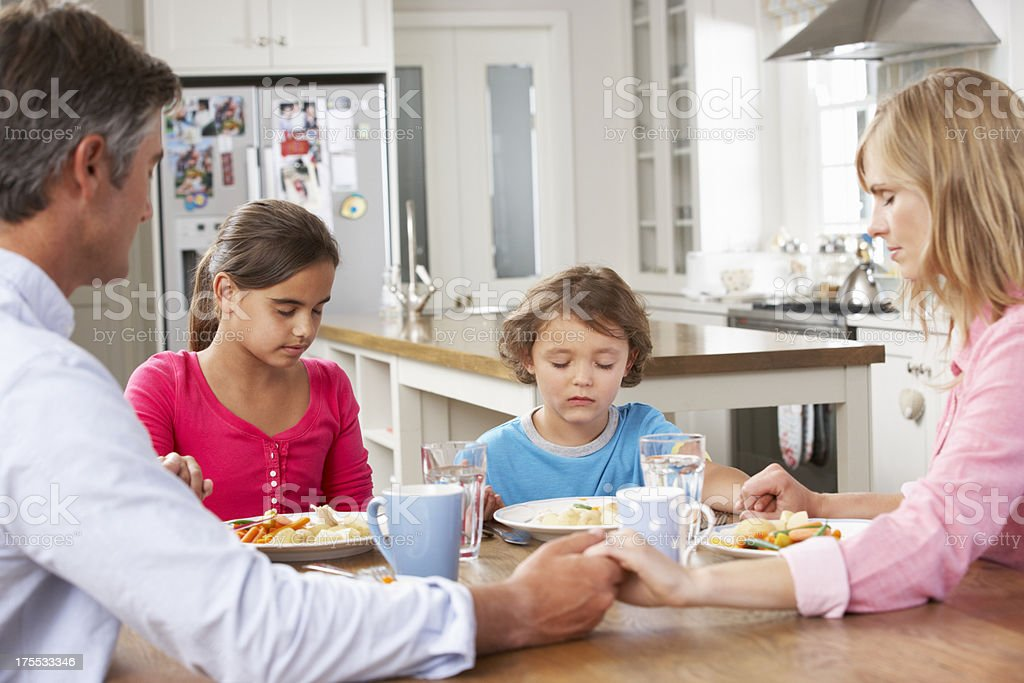 Family Praying Before Having Meal In Kitchen stock photo