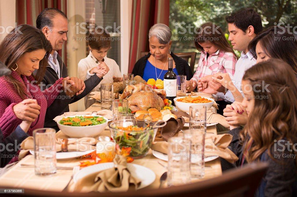 family praying around table - 986×555