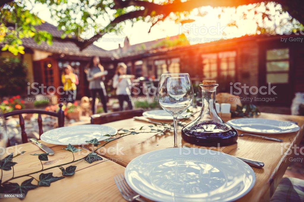 裏庭のパティオでのダイニング テーブルを準備して家族 ストックフォト
