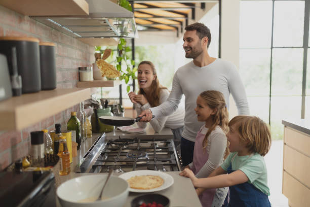 Family preparing food in kitchen at home stock photo