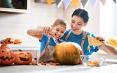 Happy Halloween! Mother and her daughter carving pumpkin. Family preparing for holiday.